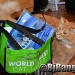 Kitty checks out World's Best Cat Litter bag chock full of goodies from CWA conference.